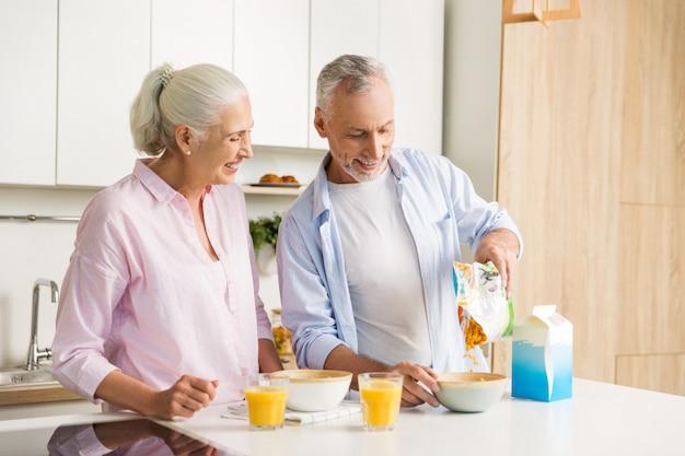 コーンフレークを食べるジュースを飲んで成熟した陽気な愛情のあるカップル家族 無料写真
