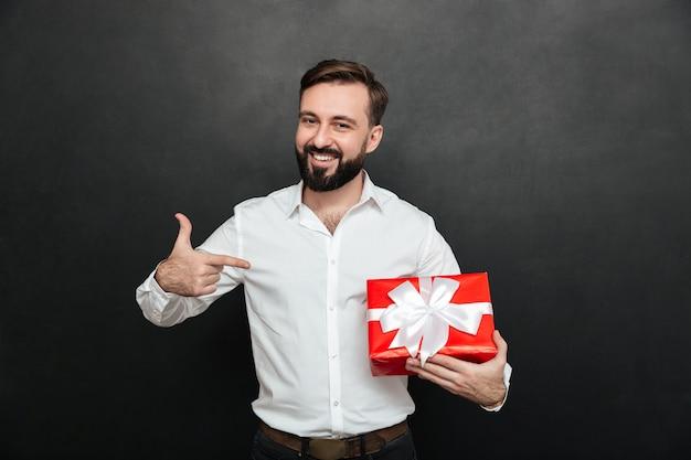 赤いギフトボックスを押しながら暗い灰色の壁に人差し指を指している幸せなひげを生やした男の肖像 無料写真