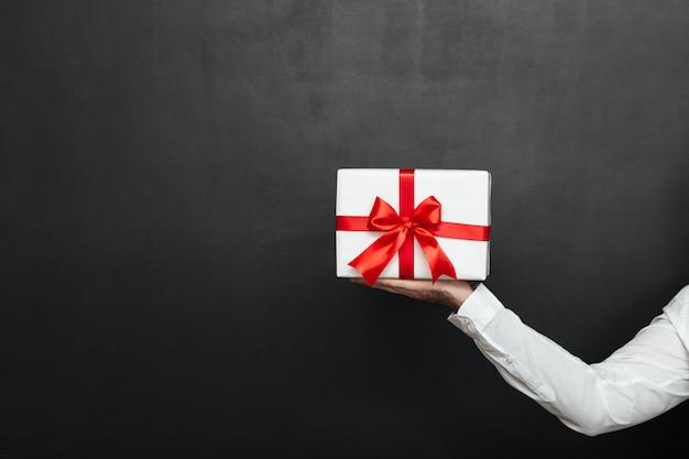 暗い灰色の壁に分離された赤い弓と白いプレゼントボックスを持っている男性の手をトリミング 無料写真
