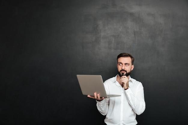 Сконцентрированный небритый парень смотрит вверх и касается подбородка, изолированного над темно-серой стеной Бесплатные Фотографии
