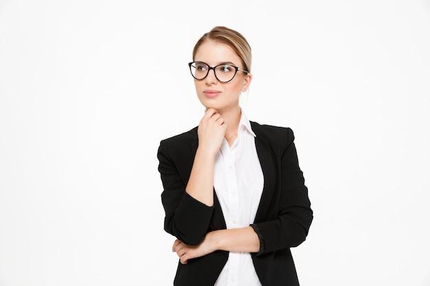 あごの近くの手を握って、白でよそ見眼鏡の魅力的な若い金髪ビジネス女性 無料写真