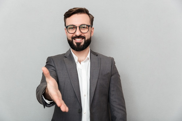 グレーで分離された握手を提供する誠実な笑顔でカメラを探している眼鏡でフレンドリーな優しい男の肖像画間近します。 無料写真