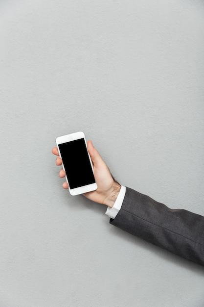 Обрезанное фото мужской руки, держащей смартфон с пустой экран, изолированные на сером, копией пространства Бесплатные Фотографии