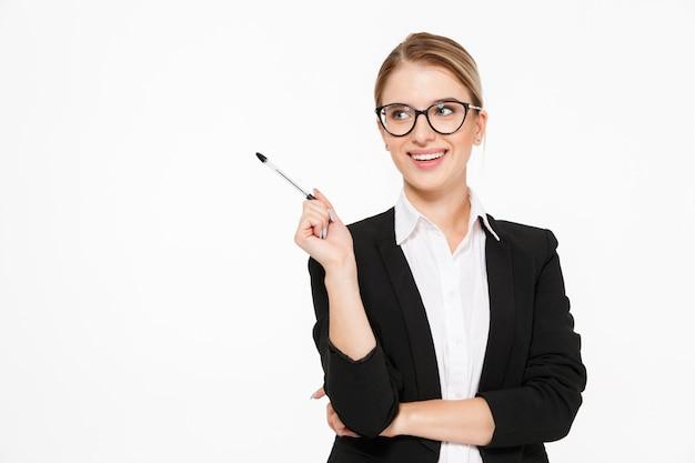 Счастливая белокурая бизнес-леди в очках с ручкой в руке имея идею и смотря прочь над белой стеной Бесплатные Фотографии