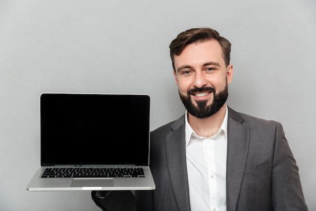 Картина довольный бородатый мужчина держит серебряную тетрадь демонстрации или рекламы на камеру, изолированных на серую стену Бесплатные Фотографии