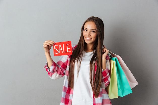 Усмехаясь красивая кавказская женщина держа знак продажи и хозяйственные сумки Бесплатные Фотографии
