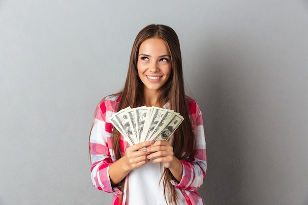 Портрет улыбающейся женщины, держащей доллары Бесплатные Фотографии