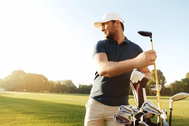 Человек гольфист, вынимая гольф-клуб из сумки Бесплатные Фотографии