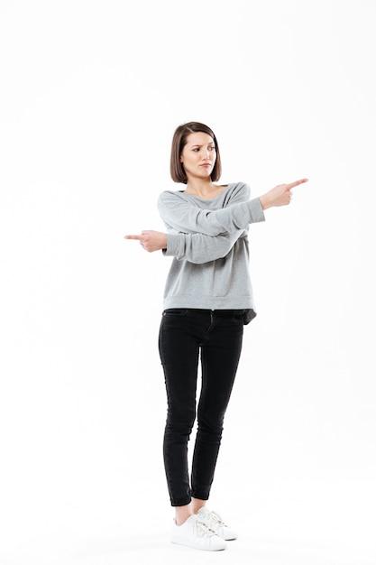 両方の方法で指を指している欲求不満の若い女性 無料写真