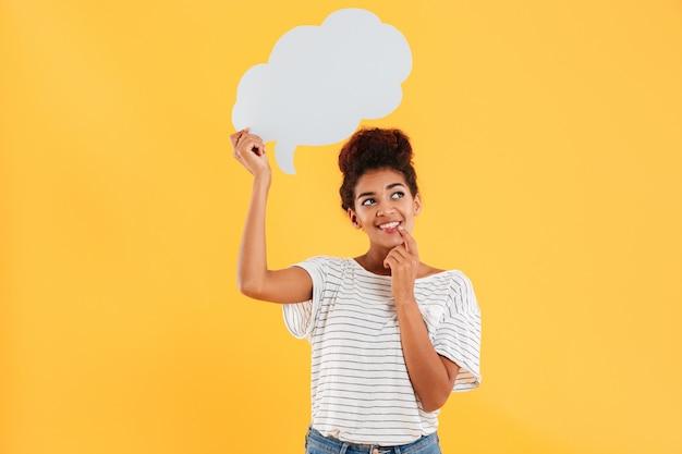 Молодая африканская счастливая заботливая дама смотря вверх и держа пустой пузырь речи изолированный над желтым цветом Бесплатные Фотографии