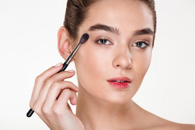 ブラシで絵の目をメイクアップを適用する健康な肌と美しい女性のポートレートを閉じます 無料写真