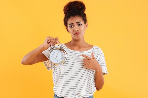 目覚まし時計を保持し、それらを指しているアフリカの女性を混乱させる 無料写真