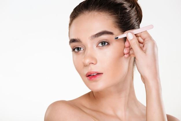 ピンセットで眉毛を摘採柔らかい肌を持つ若いブルネットの女性の肖像画 無料写真