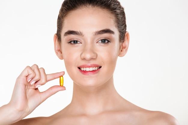 Портрет красоты усмехаясь здоровой женщины с темными волосами держа лекарства капсулы или витамин в ее представлять руки Бесплатные Фотографии