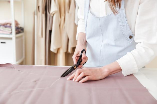 Женщина, используя ножницы, чтобы разрезать ткань Бесплатные Фотографии