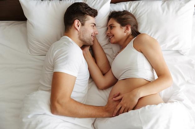 陽気な妊娠中の女性は夫とベッドにあります。 無料写真