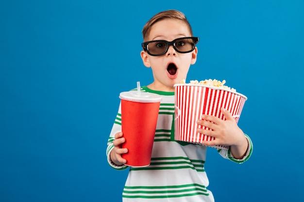 映画を見る準備をしている眼鏡のショックを受けた少年 無料写真