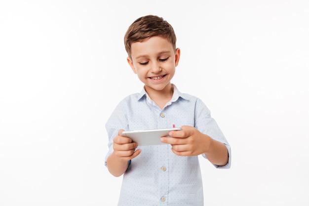 スマートフォンでゲームをプレイかわいい子供の肖像画 無料写真