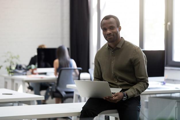 彼の机の上に座って笑顔幸せなアフロアメリカンビジネスマン 無料写真