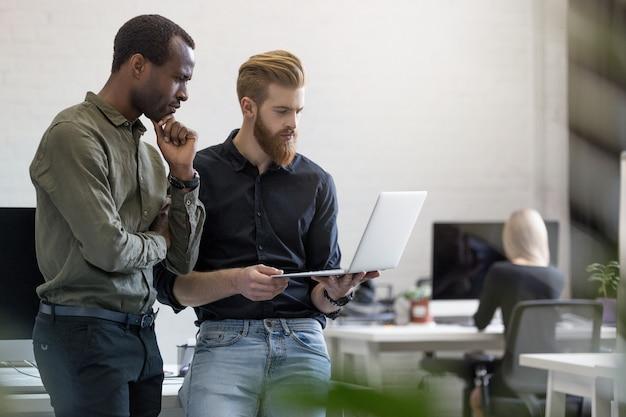 Два обеспокоенных молодых бизнесменов смотрят на ноутбук Бесплатные Фотографии