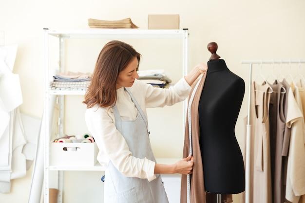 Брюнетка-швея в фартуке меряет красивую ткань на черном манекене в мастерской Бесплатные Фотографии