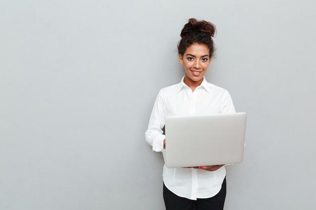 灰色の壁の上に立っているアフリカの陽気なビジネス女性 無料写真
