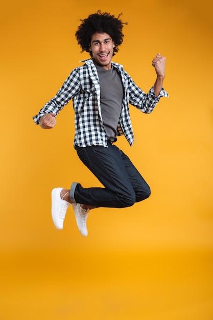 ジャンプ幸せな若いアフリカ人の完全な長さの肖像画 無料写真