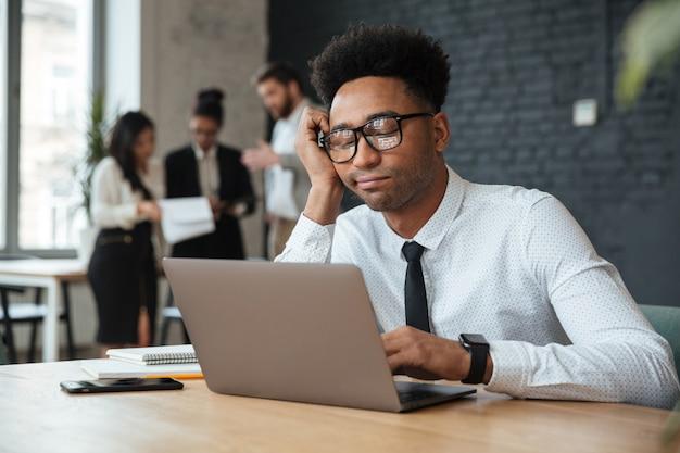 ラップトップコンピューターを使用して疲れている若いアフリカの実業家 無料写真