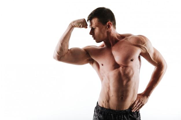 彼の上腕二頭筋を見て若い半分裸のボディービルダーのクローズアップの肖像画 無料写真