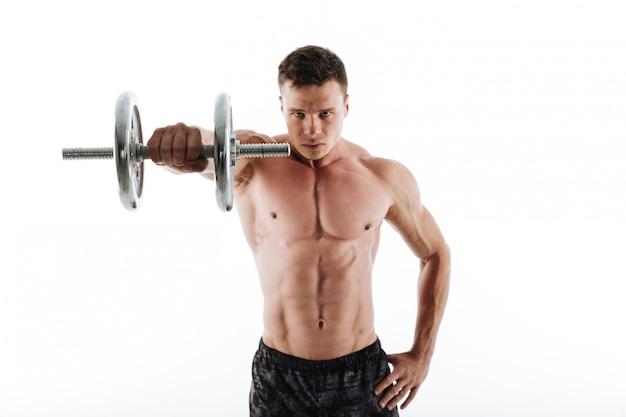 ダンベルで深刻な筋肉青年運動のクローズアップの肖像画 無料写真