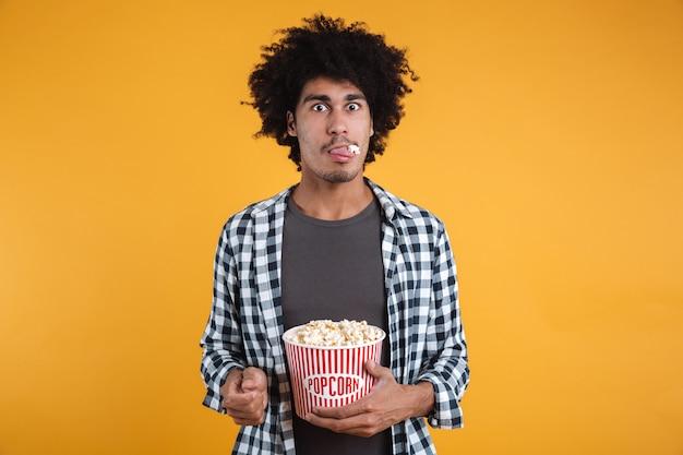 Портрет забавного афроамериканца, едящего попкорн Бесплатные Фотографии