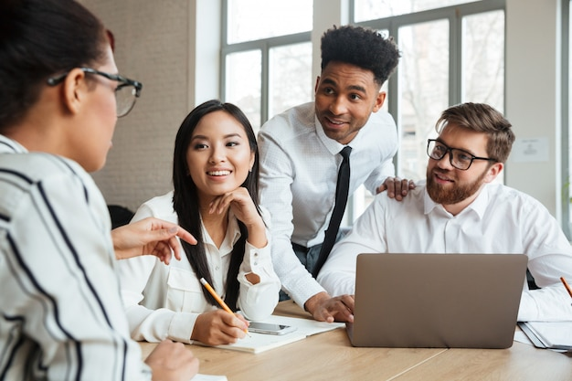 Счастливые молодые коллеги дела используя портативный компьютер разговаривая друг с другом. Бесплатные Фотографии