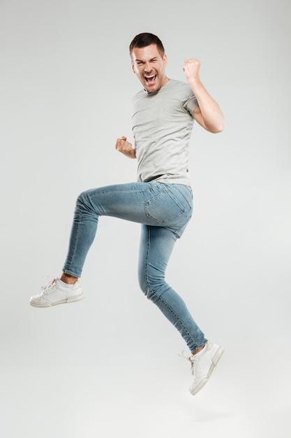 男は勝者のジェスチャーとジャンプをします。 無料写真