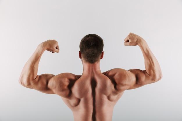 Спортсмен, стоя показывая бицепс. Бесплатные Фотографии