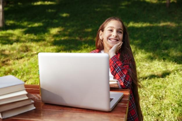 ノートパソコンとテーブルのそばに座って笑っている若いブルネットの少女 無料写真