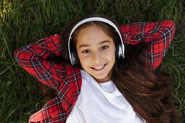 草の上に横たわる笑顔若いブルネットの少女のトップビュー 無料写真