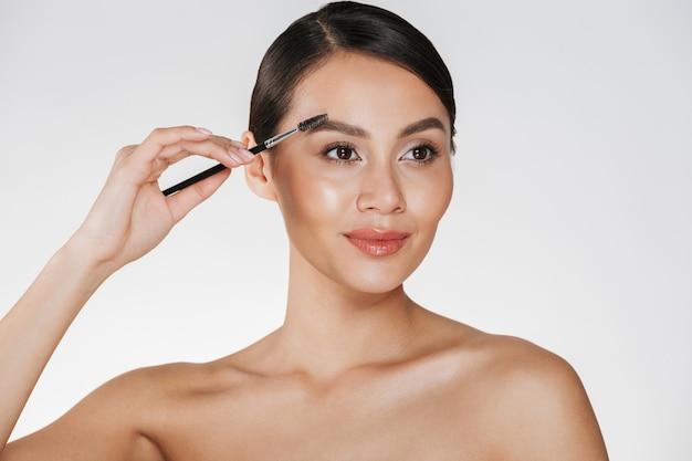 白で分離された化粧ブラシで彼女の眉毛を塗る柔らかい肌と美しいブルネットの女性のスタジオポートレートを閉じます 無料写真