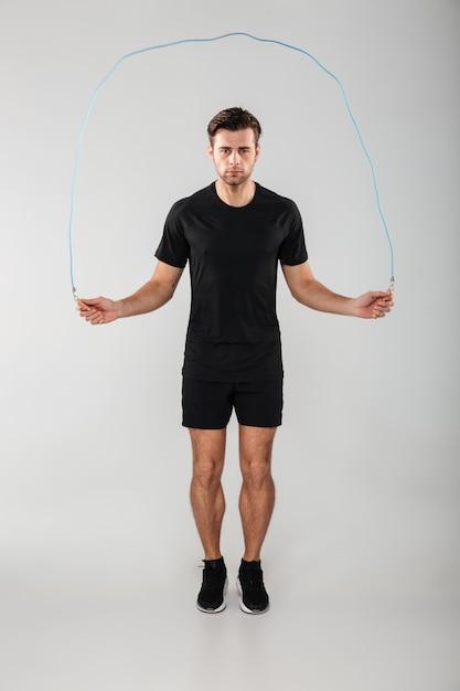 Сильный молодой спортивный человек прыгает со скакалкой Бесплатные Фотографии