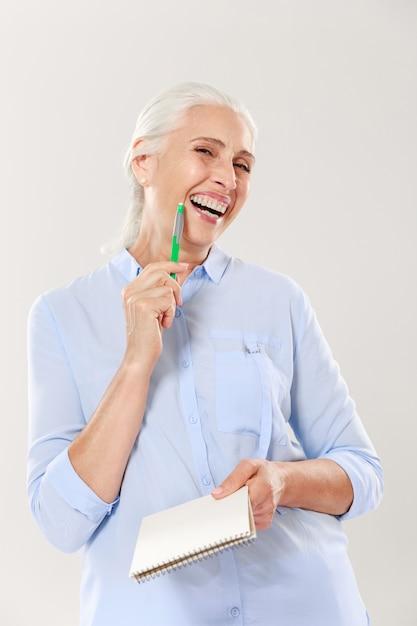 ペンとノートを探して、笑顔で幸せな女 無料写真