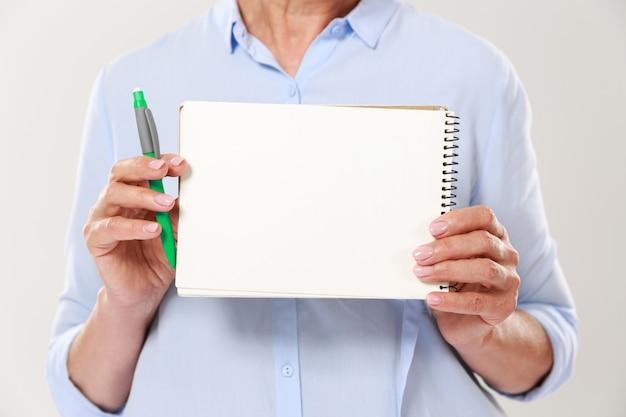 Обрезанный снимок женщины в повседневную одежду, держа ноутбук, изолированные Бесплатные Фотографии