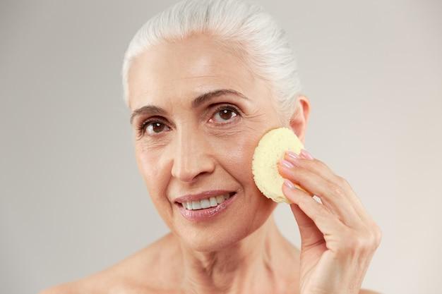 Портрет красоты усмехаясь наполовину нагой пожилой женщины используя губку состава на ее стороне и смотря камеру Бесплатные Фотографии