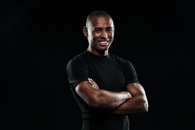 腕を組んでカメラ目線で笑顔のアフロアメリカンスポーツ男の肖像 無料写真
