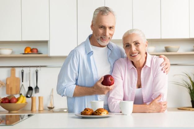 陽気な成熟した愛情のあるカップル家族が台所に立っています。 無料写真