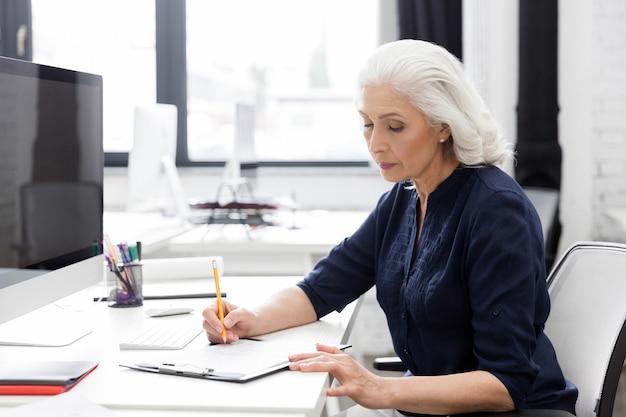 一枚の紙にメモを作る成熟したビジネス女性 無料写真