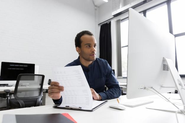 彼の机に座っている若いアフリカビジネス男 無料写真