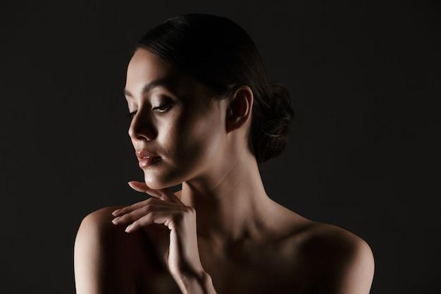 黒の上分離された低照度で彼女のあごに触れている間よそ見官能的な美しい女性の肖像画 無料写真