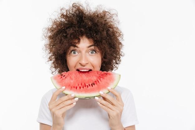 スイカを食べる巻き毛を持つ幸せな若い女性 無料写真