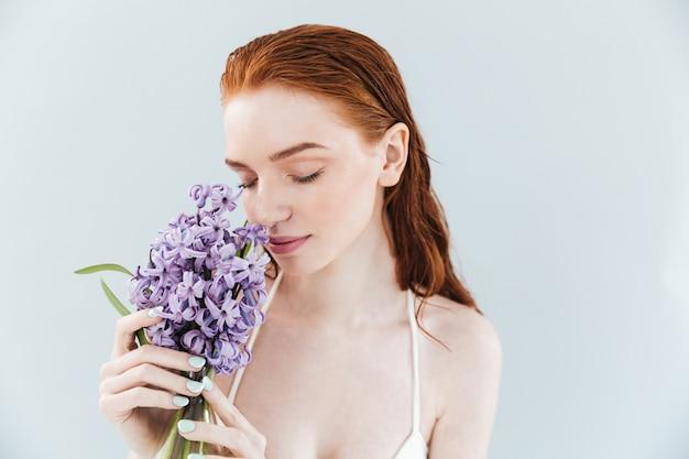 ヒヤシンスの花の臭いがする生姜女性のポートレートを閉じます 無料写真