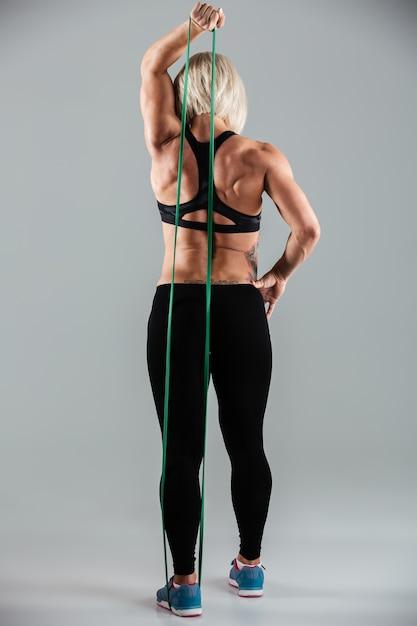 弾性ゴムで手を伸ばすスポーツウェアの女性アスリートの全長 無料写真