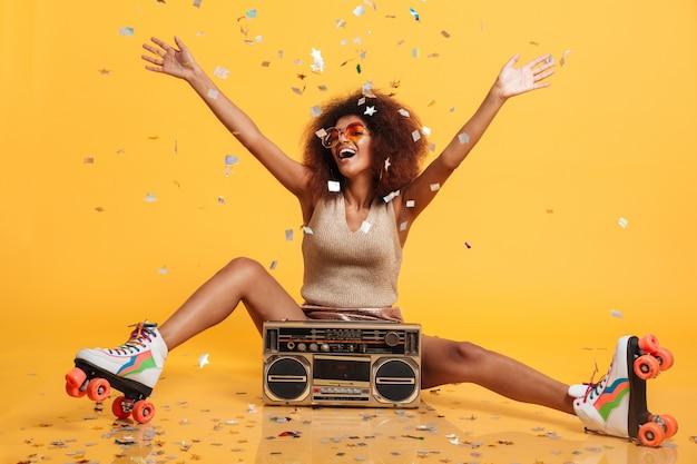 ラジカセと座っている間レトロな摩耗と紙吹雪を投げるローラースケートで魅力的な若いアフリカ人女性 無料写真